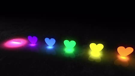 apaixonado : The dark background. Multi-colored spotlights shining heart-shaped appear from the floor and climb up. In their place rise glowing words I love you Stock Footage