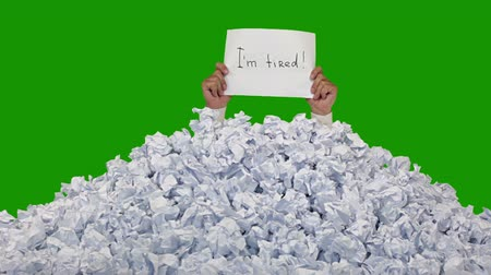papelada : Green background (Chroma Key). New crumpled paper ball are added to the heap one by one. Mens hands in a white shirt lifted a sheet of paper with words Im tired. Includes matte Stock Footage
