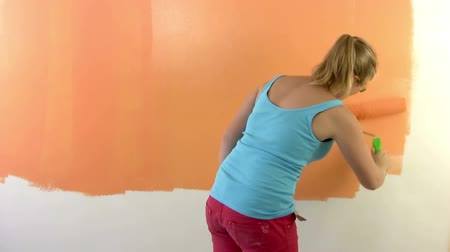 zeď : Girl paints a wall in orange with a paint roller. At the end, puts his signature :) Timelapse