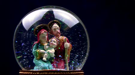 jezus : Joseph and Mary with baby Jesus in her arms. Glass ball with toy figures on a black background. The blizzard of multicolored sequins