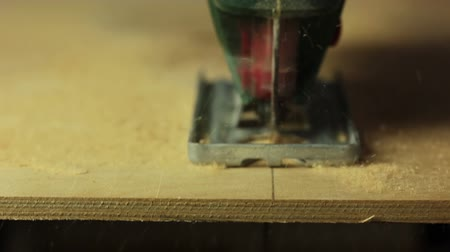 marangoz : Electric fretsaw is sawing plywood. Close-up. Front view. The end of sawing