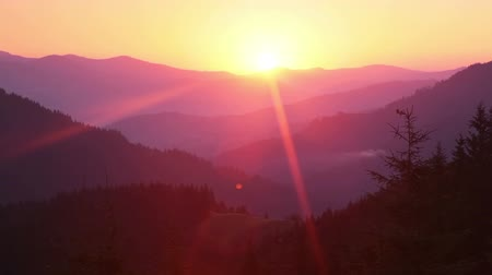 Old Carpathian mountains, covered with forests. Sunrise and long sunrays. Time lapse