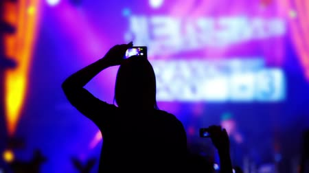 gece kulübü : Night rock concert. Many lighting effects. Many spectators. Unrecognizable silhouette of a girl with a smartphone in hand Stok Video