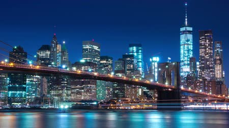 USA. New York City. Evening. View of the Manhattan skyline, East river and Brooklyn bridge. The lights of the skyscrapers are turns on. Time lapse 4K