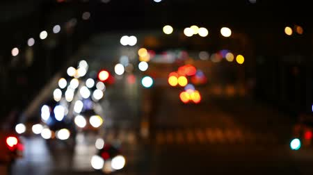 боке : City intersection at night. Many cars, buses. A few pedestrians. Defocusing