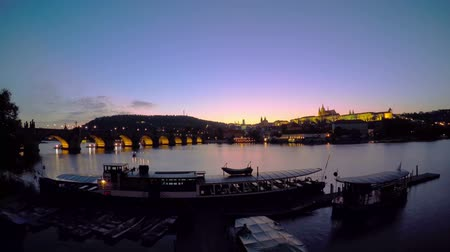cseh : Czech Republic. Prague. The view of the Prague Castle and Vltava river. Sunset. Pleasure boats and night lights. Time lapse