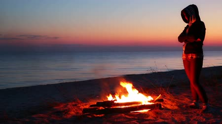 kamp ateşi : Beach just after sunset. Campfire and strong winds. Unrecognizable girl standing around the fire