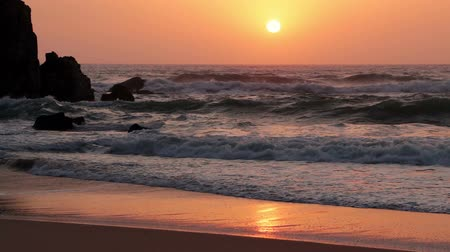 surfovat : Sandy beach and rock. The ocean surf and the sunset over the infinite ocean. Slow motion Dostupné videozáznamy
