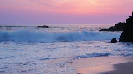 sand lia : Sandy beach among the black rocks. The surf wave and the color sky after sunset Stock Footage