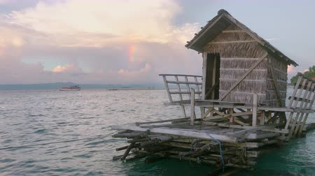 jangada : Indonesia. Evening on the tropical island. Amazing clouds and a piece of rainbow. Hut on the raft in the foreground Vídeos