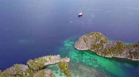 архипелаг : Indonesia. Raja Ampat archipelago from a birds eye view. Boats, turquoise shallows and small rocky islands, overgrown with rainforest. Aerial view