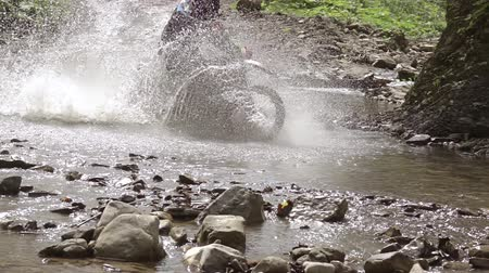 waterrad : Enduro. Motocrossman rijdt door de rivier. Spatten in de zon. Slow motion Stockvideo
