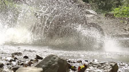 enduro : Summer sunny day. A motor rider is forcing a small river. A lot of water splashes in the sunlight. Slow motion
