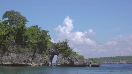 arch rock : Indonesia. Sunny weather. Small rocky island with a stone arch. Clouds swirl Fast motion