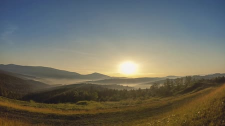 Summer morning Light fog in the valley between low mountains. Cloudy blue sky. Time lapse
