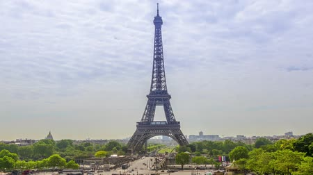eifel : France. Paris. Summer day. Traffic people and the Eiffel Tower Clouds run quickly across the sky. Time lapse