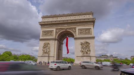 France, Paris. Square around the Arc de Triomphe. Heavy traffic. Clouds run fast. Time lapse