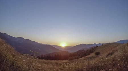 Low summer mountains. Clear sky. The sun rises. Time lapse 動画素材