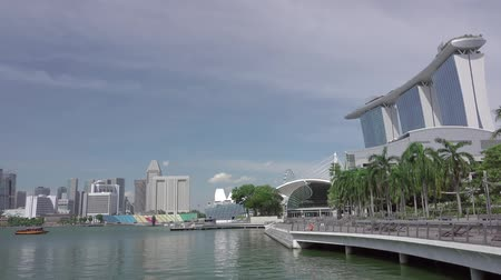 Day in Singapore. Marina Bay and the pedestrian area with palm trees. Fast motion
