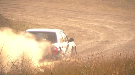 Sunny summer day. Rally track. The car passes a sharp turn. A lot of dust. Slow motion Стоковые видеозаписи