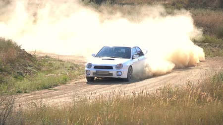 Rally track. Sunny summer day. The car passes a sharp turn. A lot of dust. Slow motion Стоковые видеозаписи