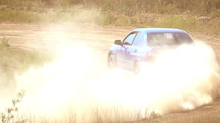 poros : Summer sunny day. Dusty dirt road. Rally car makes an extreme turn. Slow motion