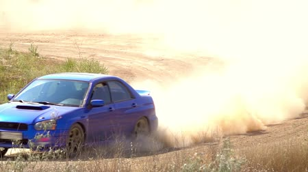 Summer sunny day. Turn of a dirt road. Unrecognizable sports car rides and raises a lot of dust. Slow motion Стоковые видеозаписи