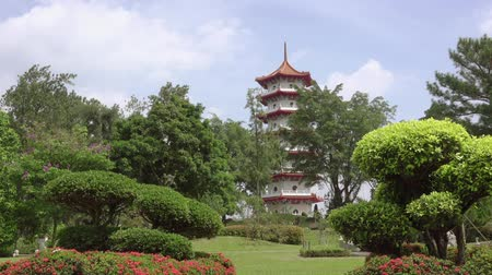 Summer sunny day in a Singapore park. Pagoda among green trees and flower beds. Clouds run fast. Time lapse