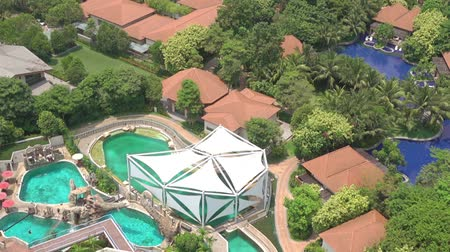 Tropical resort by the ocean. Roofs of bungalows, pools and many trees. Aerial view 動画素材
