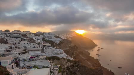 УВР : Greece. Santorini island. White houses in Oia on the island of Santorini. Yachts and catamarans in the anchorage. Dawn Clouds run fast. Time lapse Стоковые видеозаписи