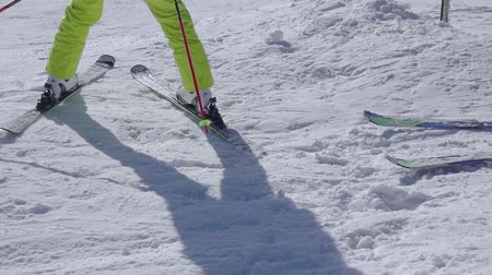 Sunny snow slope. A beginner skier makes a turn. Skiing close up. Slow motion