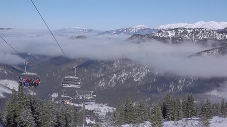 snowboard : Slovakia. Ski resort Jasna. Top view of the valley between the mountains and the ski lift. Light fog at the mountain peaks level. Slow motion Wideo