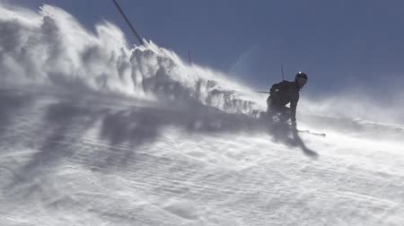 경사 : Windy weather on a sunny ski slope. Unrecognizable skier raises a lot of snow dust. Slow motion