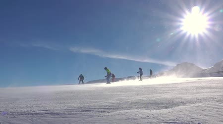 Snowstorm on a ski slope. Blue sky and sun. Several skiers and a snowboarder. Slow motion Стоковые видеозаписи
