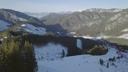 faház : Winter Slovakia. Ski resort Jasna. Skiers ride on a snowy track in wooded mountains. Aerial view Stock mozgókép