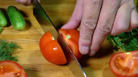 укроп : Wooden cutting board. Fresh vegetables: bell pepper, cucumbers, parsley, dill. A knife in male hands cuts a tomato. Close up. Slow motion