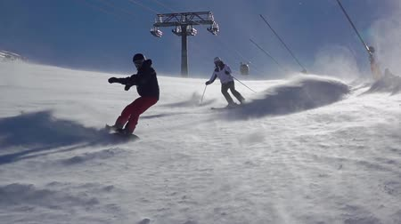 Winter sunny day on the ski slope. Unrecognizable snowboarder and skier makes a lot of snow dust in the sun backlight. Ski lift in the background. Slow motion Стоковые видеозаписи