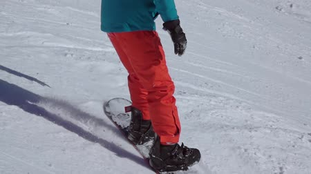 Ski resort. A snowboard in a red-blue suit goes down the ski slope. Slow motion