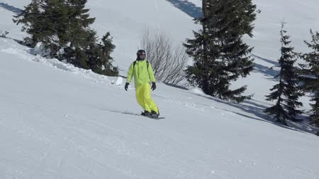 Ski resort. A snowboard in a yellow suit goes down the ski slope. Slow motion