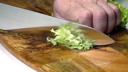Wooden cutting board. A knife in male hands cuts a bunch of salad. Close up. Slow motion Стоковые видеозаписи