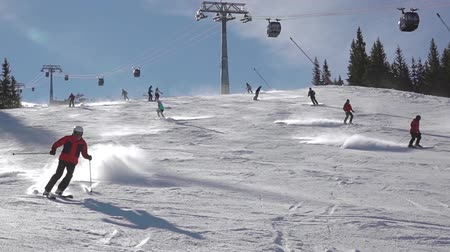 Ski resort in sunny weather. Several skiers ski downhill. Slow motion