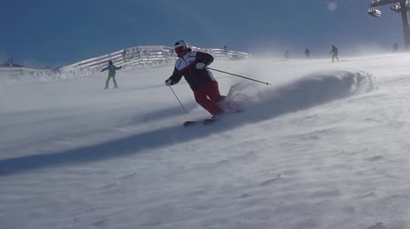 быстрый : Winter sunny day. Snowstorm on the ski slope. A skier makes a lot of snow dust. Slow motion