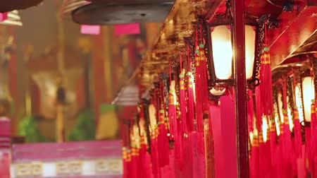 Interior of a Buddhist temple in defocus. Incense smoke. Lantern and red ribbons swing from the wind Стоковые видеозаписи
