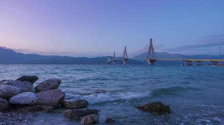 Greek cable-stayed bridge over the Gulf of Corinth. Rion-Antirion. Clear evening sky over the mountain shore. Time lapse Стоковые видеозаписи
