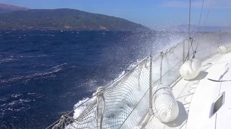 Sunny windy day. White sailing yacht floats in the waves and creates a cloud of sea spray. Slow motion Стоковые видеозаписи