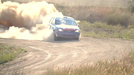 rali : Summer day. Bright sunshine. Rally car drives through a turn with a skid and a lot of dust. Slow motion