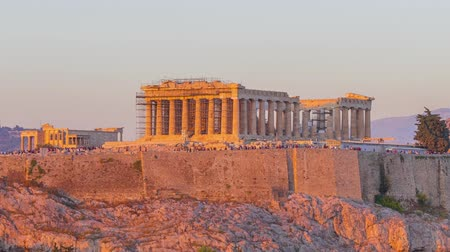 акрополь : Greece. Athens. Cloudless evening. Tourists leave the ruins of the Parthenon and night lights turn on. Time lapse. Zoom out