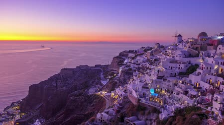 УВР : Greece. White houses and roofs on the island of Santorini (Thira). Many boats with tourists go to sea to meet the sunset. Time lapse