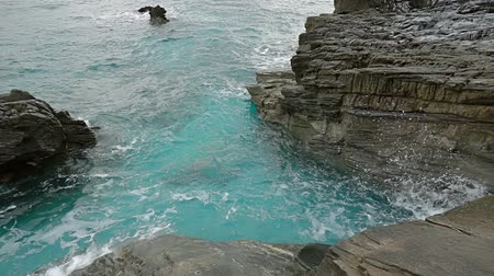 Small bay between coastal cliffs with turquoise water. The wave makes a lot of spray. Slow motion