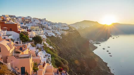 УВР : Greece. Volcanic island of Thira (Santorini). Cloudless dawn over the caldera. Many white houses of Oia city on the side of a mountain and a yacht in the harbor. Time lapse Стоковые видеозаписи